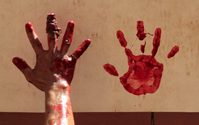 A butcher makes hand prints on the wall from the blood of a just-slaughtered calf on the first day of Eid al-Adha festival in Toukh, El-Kalubia governorate, northeast of Cairo, Egypt, September 24, 2015. (Photo by Amr Abdallah Dalsh/Reuters)