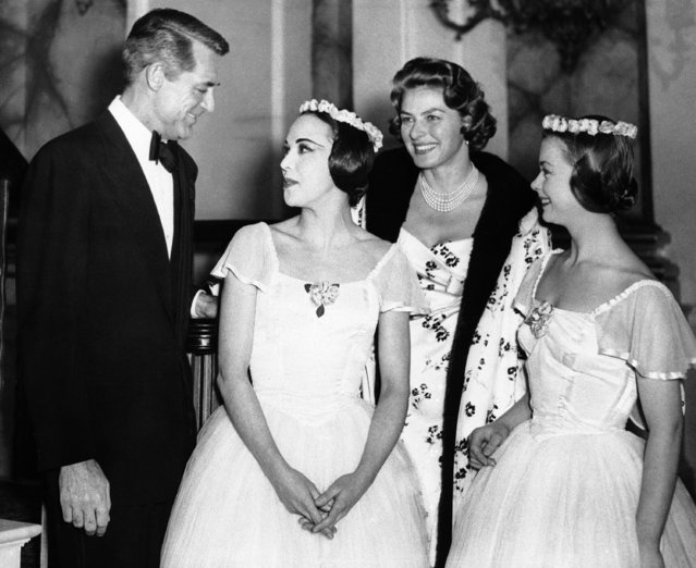 """American actor Cary Grant, left, and Swedish-born actress Ingrid Bergman (second from right) chat with two Australian ballerinas, Margaret Lee and Brenda Bolton, right, at the Royal Opera House, Covent Garden, London on December 9, 1957, during the shooting of a scene from the new film """"Indiscreet"""", in which Grant and Miss Bergman are co-stars. The film is based on the play """"Kind Sir"""" by Norman Krasna. (Photo by AP Photo)"""