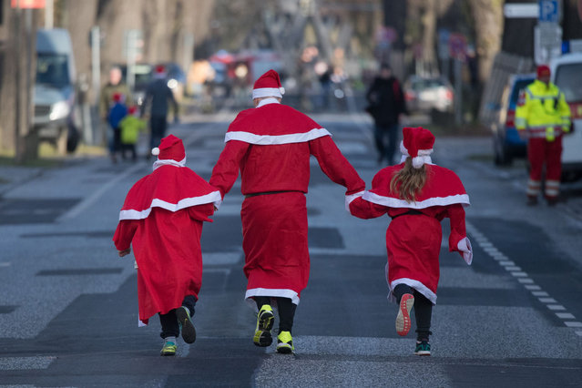 Participants dressed in Father Christmas costumes take part in the traditional Santa Claus run in Michendorf, eastern Germany, on December 10, 201. (Photo by Ralf Hirschberger/AFP Photo/DPA)