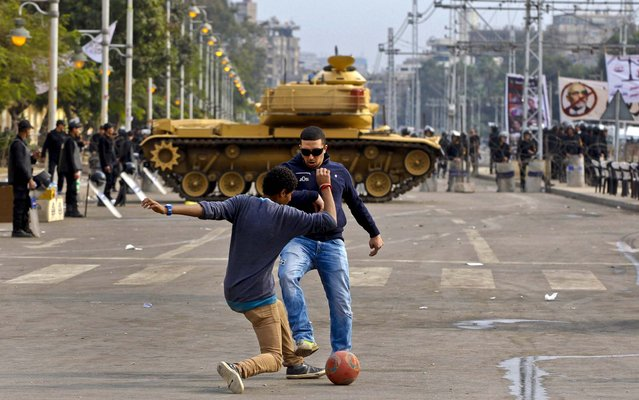 Protesters play with a ball in front of a tank securing the area around the presidential palace in Cairo, Egypt, December 14, 2012. Opposing sides in Egypt's political crisis were staging rival rallies on the final day before voting starts on a contentious draft constitution that has plunged the country into turmoil and deeply divided the nation. (Photo by Petr David Josek/Associated Press)