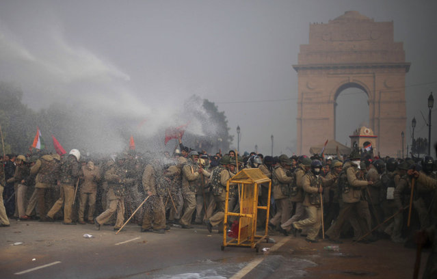 Indian policemen are sprayed with police water cannon aimed at protestors during a violent protest in New Delhi, on December 23, 2012. (Photo by Altaf Qadri/AP Photo)