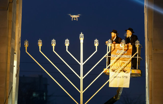 Kazakhstan's chief Rabbi Eshaya Cohen and Almaty chief Rabbi Ilchanan Cohen are lifted on a hoist to light the eighth candle during a celebration of the Jewish holiday of Hanukkah in the centre of Almaty, Kazakhstan December 19, 2017. (Photo by Shamil Zhumatov/Reuters)