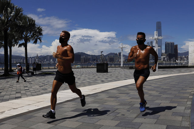 Two men wearing face masks run at a park in Hong Kong, Thursday, July 30, 2020. Hong Kong banned dining-in at restaurants completely on Wednesday and made it mandatory to wear masks in all public places, as the city battles its worst coronavirus COVID-19 outbreak to date. (Photo by Kin Cheung/AP Photo)