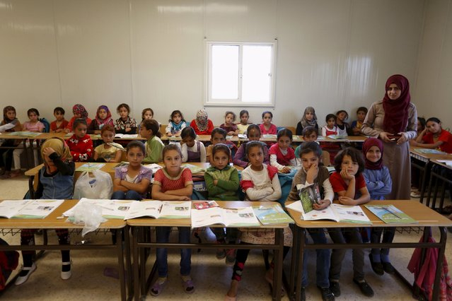 Teacher Hanan Anzi poses for a picture with Syrian refugee students inside their classroom at one of the UNICEF schools at Al Zaatari refugee camp in the Jordanian city of Mafraq, near the border with Syria, September 22, 2015. (Photo by Muhammad Hamed/Reuters)