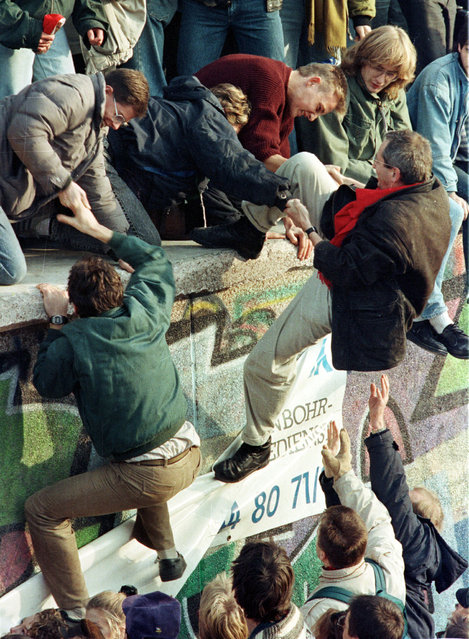 East German citizens help each other climb the Berlin Wall at the Brandenburg gate after the opening of East German borders, November 10, 1989. (Photo by Reuters)