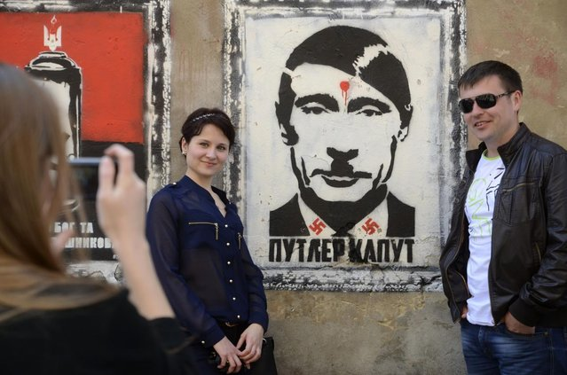 "People pose for a picture next to graffiti reading ""Putler kaput"" in Lviv, Ukraine May 9, 2014. (Photo by Reuters/Stringer)"