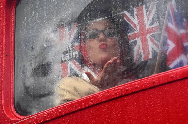 A woman gestures through a bus window as visitors and car enthusiasts attend the annual Goodwood Revival historic motor racing festival, celebrating a mid-twentieth century heyday of the racing circuit, near Chichester in south England, Britain September 10, 2016. (Photo by Toby Melville/Reuters)