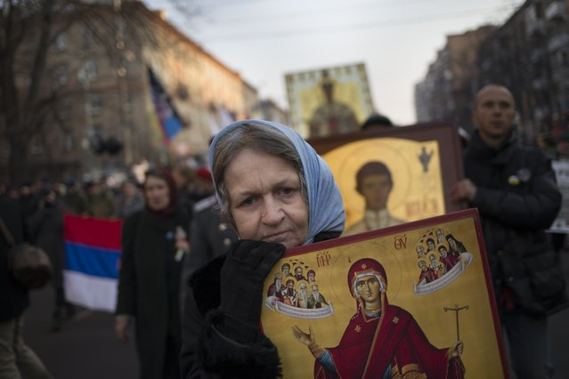 Russian nationalists carry Orthodox icons during a march in support of pro-Russian separatists fighting with Ukrainian government forces in eastern Ukraine in Moscow to mark People's Unity Day, a public holiday in Russia, on Tuesday, November 4, 2014. (Photo by Alexander Zemlianichenko/AP Photo)