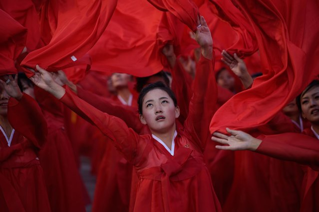 Dancers perform during a mass military parade at Kim Il-Sung square in Pyongyang on October 10, 2015. (Photo by Ed Jones/AFP Photo)