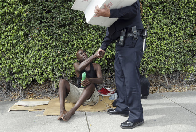 Lorenzo Ward, 45, who is homeless, shakes hands with Miami police officer James Bernat, after Bernat gave him a can of insect repellent, Tuesday, August 2, 2016 in the Wynwood neighborhood of Miami. The CDC has advised pregnant women to avoid travel to this neighborhood where mosquitoes are apparently transmitting Zika directly to humans. Bernat passed out some fifty cans of spray to the homeless. (Photo by Lynne Sladky/AP Photo)