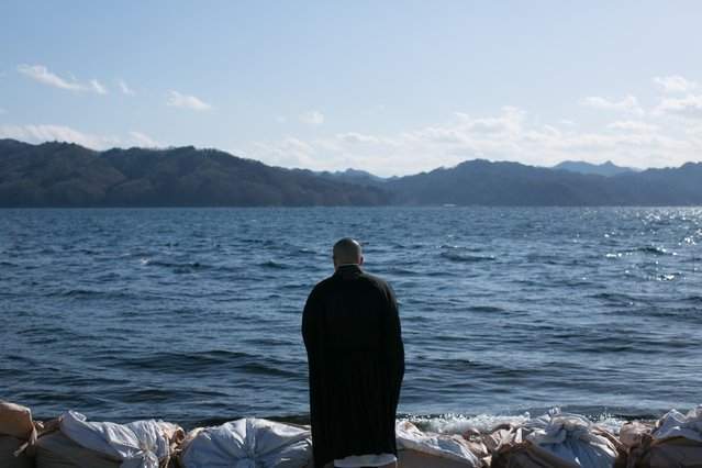 A Buddhist monk prays toward the sea on March 11, 2013 in Ootsuti, Iwate prefecture, Japan. On March 11 Japan commemorates the second anniversary of the magnitude 9.0 earthquake and tsunami that claimed more than 18,000 lives. (Photo by Ken Ishii/AP Photo)