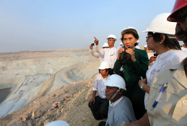 Myanmar's opposition leader Aung San Suu Kyi uses binoculars to look at the Letpadaung copper mine project during a visit to Myanmar Yang Tse Copper Limited in Monywa, 760 kilometers (450 miles) north of Yangon, central Myanmar, Thursday, March 14, 2013. In talks with villagers, Suu Kyi failed to persuade her listeners to agree with the conclusions of an official panel she headed that the national interest was best served by allowing continued operation of the Letpadaung copper mine, to encourage foreign investors to help the sagging economy. (Photo by Khin Maung Win/AP Photo)