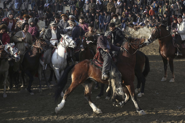 Afghan horse riders compete for the goat during a friendly buzkashi match on the outskirts of Kabul, Afghanistan, Friday, December 22, 2017. Buzkashi is a traditional and the national sport of Afghanistan, where players compete to place a goat carcass into a goal circle. It was banned during the Taliban rule. (Photo by Rahmat Gul/AP Photo)