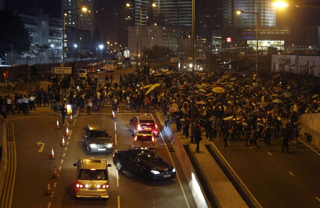 Cars turn back as pro-democracy protester block a road outside the chief executive office during a rally in Hong Kong, November 30, 2014. (Photo by Bobby Yip/Reuters)