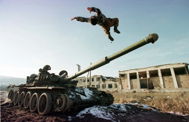 A Chechen soldier does a back flip off a Russian tank gun in the Chechen village of Bamut Friday, January 24, 1997. Elections are planned in Chechnya on Monday and the separatist leaders are campaigning to make Chechnya fully independent of Russia. (Photo by Sergei Karpukhin/AP Photo)