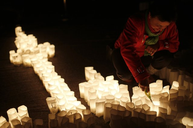 A woman ignites candles during Earth Hour in the city centre of Frankfurt March 23, 2013. Earth Hour, when everyone around the world is asked to turn off lights for an hour from 8.30 p.m. local time, is meant as a show of support for action to confront climate change. (Photo by Lisi Niesner/Reuters)