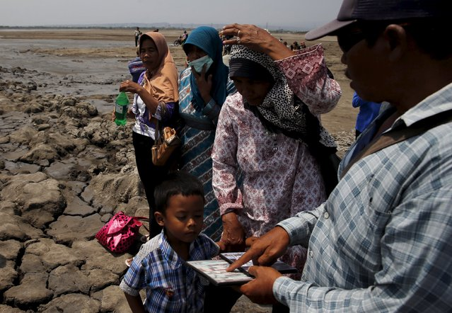 A villager (R) sells videos of the mudflow disaster to tourists at the Lapindo mud field in Sidoarjo, October 11, 2015. (Photo by Reuters/Beawiharta)