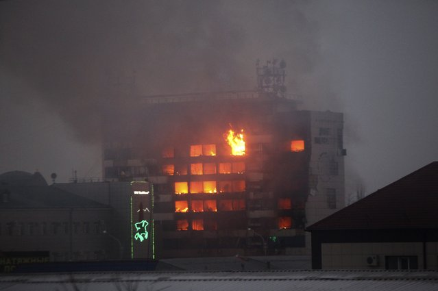 A publishing house building is seen in flames in the center of Grozny, Russia, early Thursday, December 4, 2014. A gun battle broke out after midnight Thursday in the capital of Russia's North Caucasus republic of Chechnya, puncturing the patina of stability ensured by years of heavy-handed rule by a Kremlin-appointed leader. (Photo by Musa Sadulayev/AP Photo)