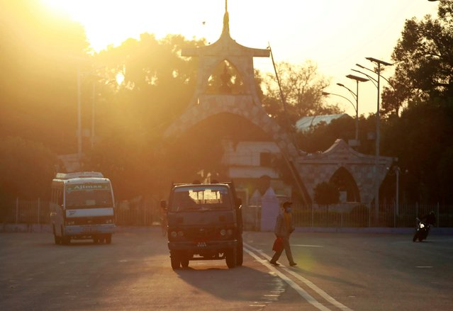 A man crosses the street as the sun rises in Kathmandu, Nepal on October 9, 2020. (Photo by Navesh Chitrakar/Reuters)
