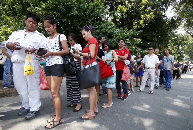 Myanmar nationals queue to cast their votes outside the Myanmar embassy in Singapore, October 15, 2015. Hundreds of voters queue up from as early as 5am outside the embassy to cast their votes for the general elections on November 8, according to volunteers. About 20000 Myanmar nationals submitted their requests for early voting according to local media. (Photo by Edgar Su/Reuters)