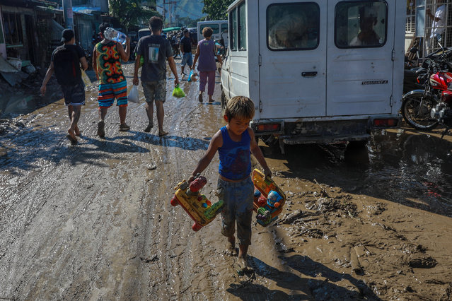 A child carries salvaged toys along a road covered in mud following Typhoon Vamco in Rodriguez, Rizal, east of Manila, Philippines, 13 November 2020. (Photo by Mark R. Cristino/EPA/EFE)