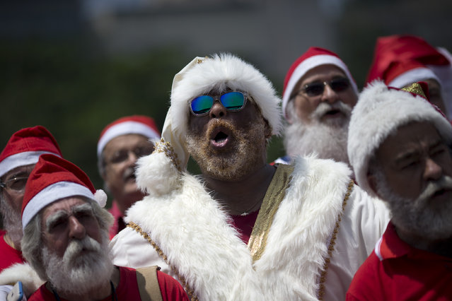 """Recent graduates of a Santa school sing Christmas carols during their graduation ceremony in Rio de Janeiro, Brazil, Tuesday, November 10, 2015. The """"Escola de Papai Noel do Brasil"""" graduated dozens of students who are now ready to be hired to play the part of Kriss Kringle during the Christmas season. (Photo by Silvia Izquierdo/AP Photo)"""