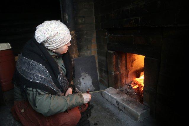 Eda Veeroja looks at the stove as the sauna heats up at Mooska farm, near the village of Haanja December 20, 2014. (Photo by Ints Kalnins/Reuters)