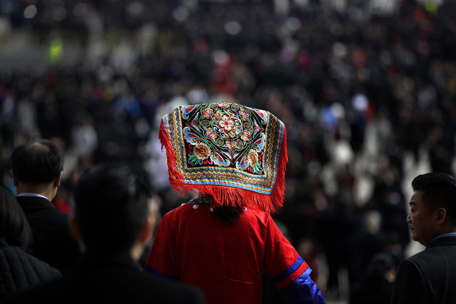 A delegate in ethnic minority costume leaves the Great Hall of the People after attending the closing session of the annual National People's Congress (NPC) in Beijing, Tuesday, March 20, 2018. (Photo by Andy Wong/AP Photo)
