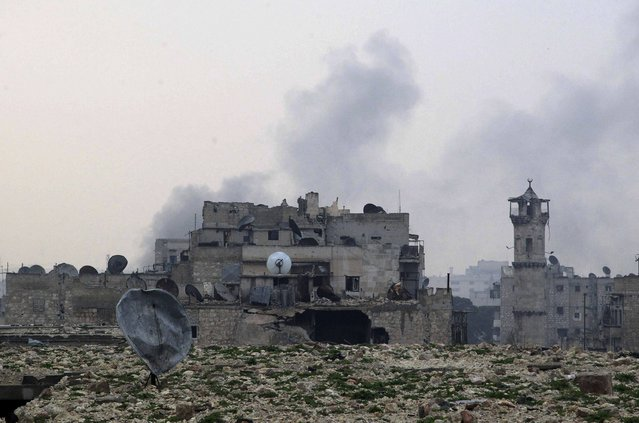 Smoke rises behind damaged buildings after what activists said was shelling by forces loyal to Syria's President Bashar al-Assad in Aleppo December 28, 2014. (Photo by Jalal Al-Mamo/Reuters)