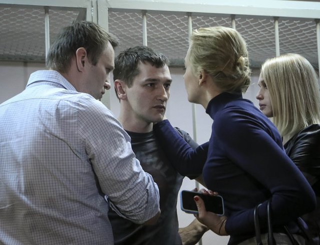 Alexei Navalny (L), Russian opposition leader and anti-corruption blogger, and his wife Yulia (2nd R) comfort Alexei's brother and co-defendant Oleg (C) next to his wife Victoria after hearing the court verdict in Moscow December 30, 2014. (Photo by Sergei Karpukhin/Reuters)