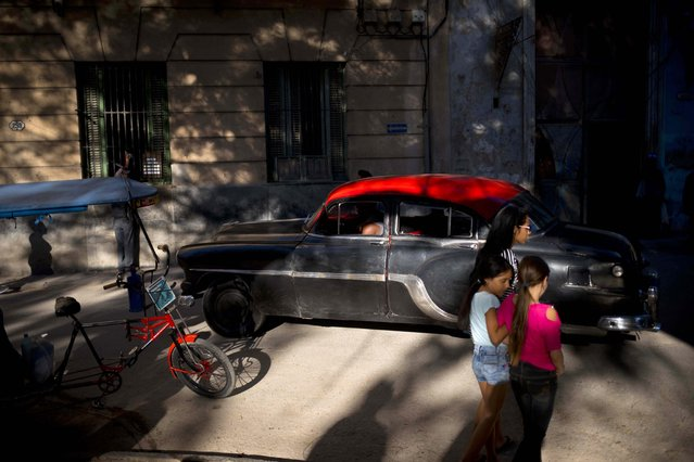 Girls walk along a street in Old Havana where a driver steers his classic American car in Havana, Cuba, Tuesday, April 17, 2018. A legislative session on Wednesday will see a historic political transition, in which President Raul Castro plans to step down and hand over the office to a younger successor. (Photo by Ramon Espinosa/AP Photo)