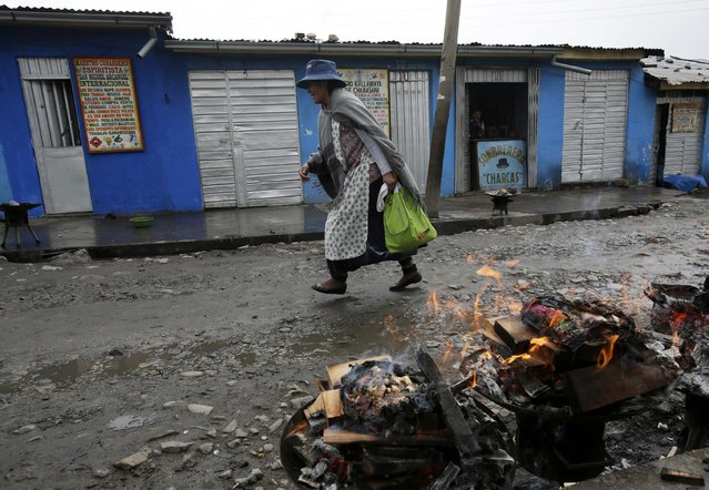 An Aymara woman walks at the witches market of El Alto, on the outskirts of La Paz, December 31, 2014. (Photo by David Mercado/Reuters)