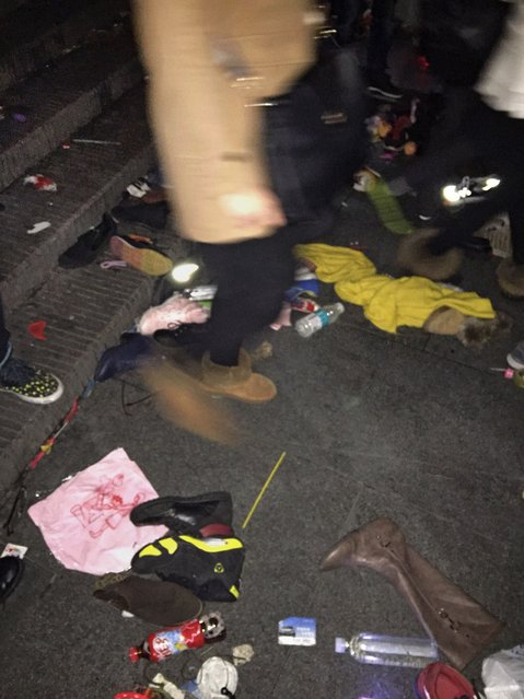 A person walks past shoes and clothing scattered on the ground after a stampede by new year revellers on Shanghai's historic riverfront to welcome the new year early on January 1, 2015. (Photo by Zhou Miaochen/AFP Photo)