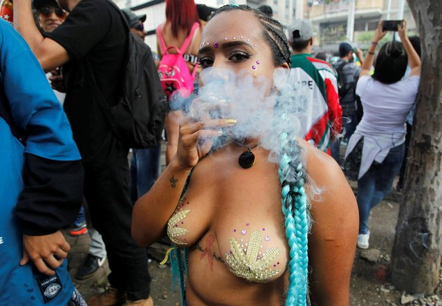 A woman smokes marijuana during a Global March for Marijuana in Medellin, Colombia, May 5, 2018. (Photo by Fredy Builes/Reuters)