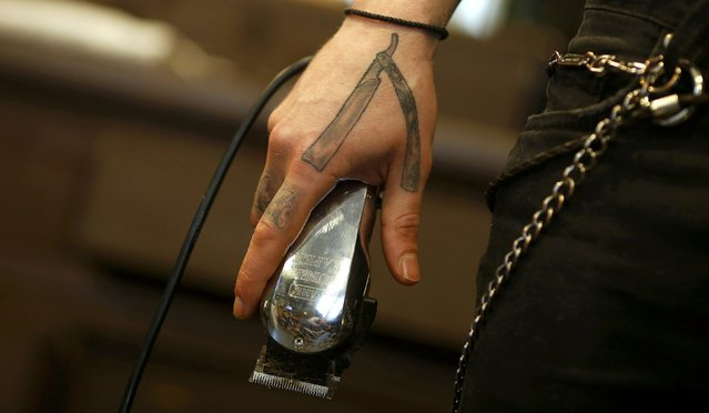 "Alex ""Torreto"" Vellios, a 26-year old barber sports his tattoo of an open razor as he holds electric clippers while preparing for his first customer of the day at his Torreto barber shop in Frankfurt, January 6, 2015. (Photo by Kai Pfaffenbach/Reuters)"