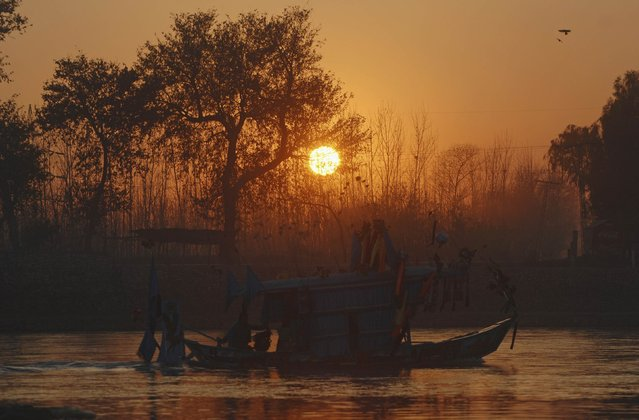 A man is silhouetted as he rows a boat during sunset at Sardaryab River in Charsadda, near Peshawar, December 31, 2014. (Photo by Khuram Parvez/Reuters)