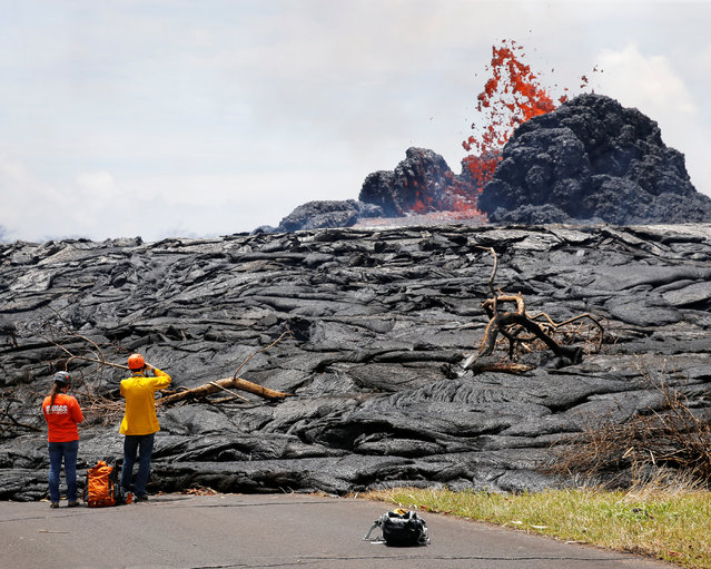 Sarah Conway, left, and Matt Patrick, both from USGS Hawaiian Volcanos, observe lava erupting from a fissure in the Leilani Estates near Pahoa, Hawaii, May 24, 2018. (Photo by Marco Garcia/Reuters)