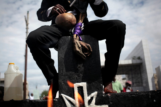 "A voodoo believer, dressed as ""Gede"", a spirit of voodoo, sits on the cross of Baron Samdi during celebrations at the cemetery of Port-au-Prince, Haiti, November 1, 2016. (Photo by Andres Martinez Casares/Reuters)"
