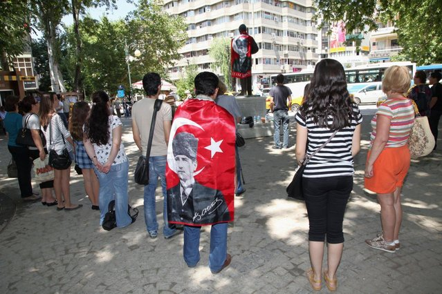 Protesters, one wearing a national flag with an image of Turkey's founder Kemal Ataturk, stand in a silent protest in Kugulu Park in Ankara, Turkey, Wednesday, June 19, 2013. After weeks of sometimes-violent confrontation with police, Turkish protesters have found a new form of resistance: standing still and silent. (Photo by Burhan Ozbilic/AP Photo)