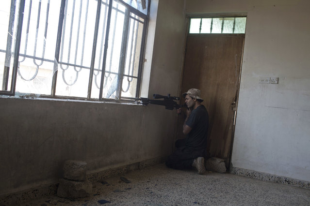 An Iraqi special forces sniper gets ready to fire at Islamic State positions on the outskirts of Mosul, Iraq, Friday, November 4, 2016. Heavy fighting erupted in the eastern neighborhoods of Mosul on Friday as Iraqi special forces launched an assault deeper into the urban areas of the city and swung round to attack Islamic State militants from a second entry point, to the northeast. (Photo by Marko Drobnjakovic/AP Photo)