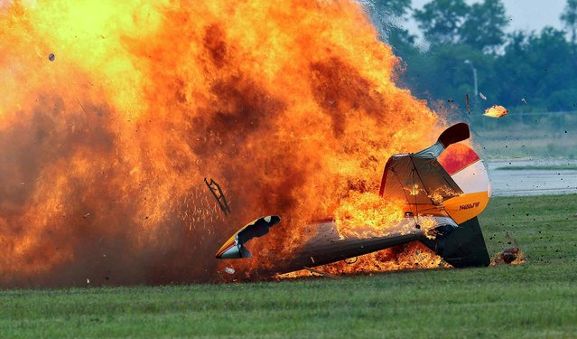 Flames erupt from the stunt plane after the crash. (Photo by Thanh V. Tran/Associated Press)