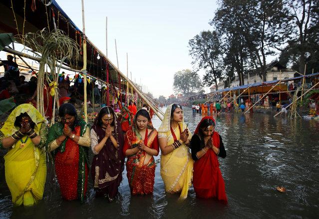 "Devotees offer prayers to the setting sun during the ""Chhat"" festival at Bagmati River in Kathmandu, Nepal November 6, 2016. (Photo by Navesh Chitrakar/Reuters)"