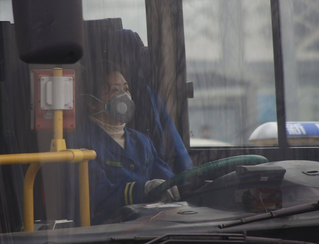 "A female driver wearing a mask drives a bus amid heavy smog after the city issued its first ever ""red alert"" for air pollution, in Beijing, China, December 8, 2015. (Photo by Kim Kyung-Hoon/Reuters)"