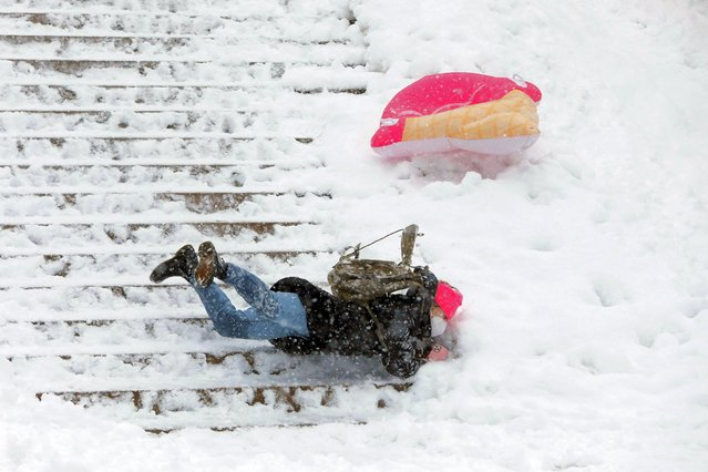 A person falls down stairs while sledding in Central Park as snow falls in Manhattan, New York City, U.S., February 7, 2021. (Photo by Andrew Kelly/Reuters)