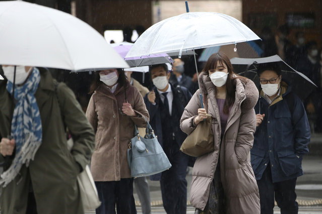 People wearing face masks to protect against the spread of the coronavirus walk at a crossing in Tokyo, Monday, February 15, 2021. Tokyo is under state of emergency as the government seeks to stop a surge of new coronavirus infections. (Photo by Koji Sasahara/AP Photo)