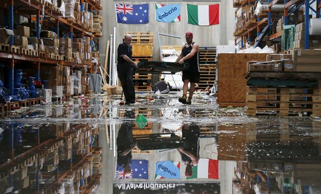 Workers at a warehouse move a crate after the building's roof was torn off during a rare tornado in the Sydney suburb of Kurnell, December 16, 2015. (Photo by Jason Reed/Reuters)