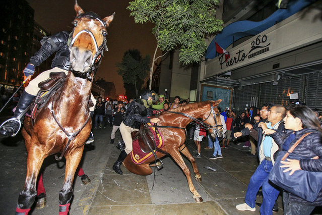 """A police horse falls to the ground during the """"Great March For a Total Reform of the Political and Judicial System"""", in Lima, Peru, 19 July 2018. The march was organized in response to recently disclosed corruption cases allegedly involving judges and members of the National Magistracy Council. (Photo by German Falcon/EPA/EFE)"""