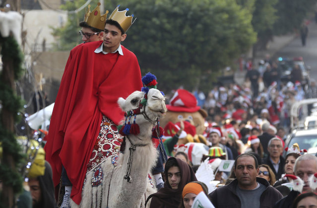 Students wearing festive Christmas costumes ride on a camel as they take part in a Christmas parade in Beirut, Lebanon, December 22, 2015. (Photo by Aziz Taher/Reuters)