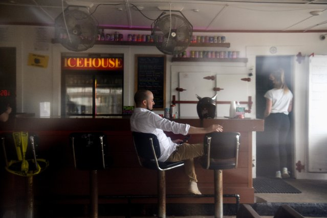 A man sits at a bar as the state of Texas prepares to lift its mask mandate and reopen businesses to full capacity during the coronavirus disease (COVID-19) pandemic in Houston, Texas, U.S., March 9, 2021. (Photo by Callaghan O'Hare/Reuters)