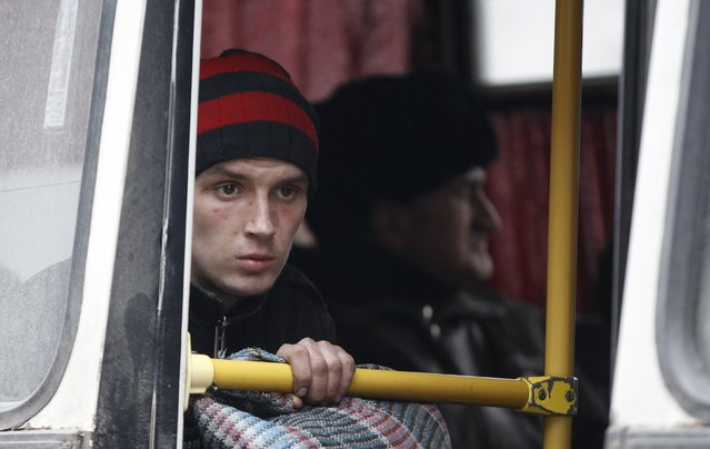 A young man waits on a bus to leave the town of Debaltseve in Artemivsk, Ukraine, Tuesday, February 3, 2015. (Photo by Petr David Josek/AP Photo)
